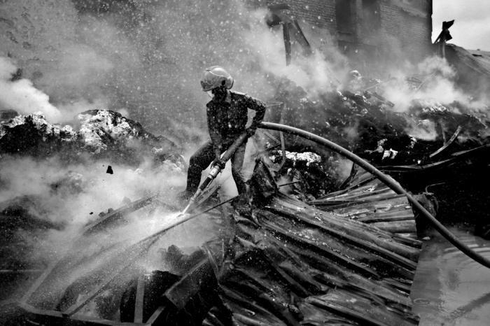 © Abir Abdullah/ European Pressphoto Agency A fireman attempts to extinguish a fire at Kung Keng textile factory. Unsafe working conditions have led to repeated accidents. Export Processing Zone, Dhaka. 26 August 2005