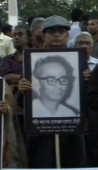 Tanvir Haide Chaudhury holds photo of his father at Shaheed Minar.