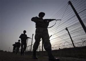 Indian BSF soldiers patrol the fenced border with Pakistan in Suchetgarh