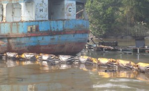 The rescued tanker surrounded by rubber boom.